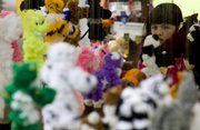 Olivia Rice, 8, is surrounded by handcrafted puppets.