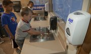 First-grade students at Deerfield School wash their hands with soap and water before lunch.