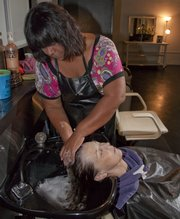 Connie Loebsack has her hair washed by Cora Carey at Head Rush Studio, 622 W. 12th St.