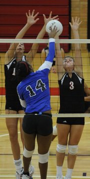 Lawrence High's Lillian Schonewise, left, and Morgan Green, right, prepare for a block against Leavenworth. The Lions defeated Leavenworth and went 2-1 at their quadrangular on Thursday at LHS.