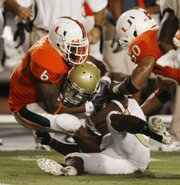 Miami's Randy Phillips (6) rips the helmet off Georgia Tech's Embry Peeples as Darryl Sharpton (50) helps him make the tackle. Miami won, 33-17, Thursday in Miami.