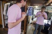Ryan Estey, an employee at Hobbs, 700 Mass., tries on a pink shirt.