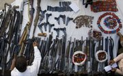 A plainclothes Pakistani police officer inspects confiscated weapons displayed for media Saturday at a police station in Islamabad, Pakistan. Pakistani police raided a local security firm that has a contract with the U.S. Embassy, seizing dozens of allegedly unlicensed weapons at a time when American use of private contractors is under unusual scrutiny here, officials said.