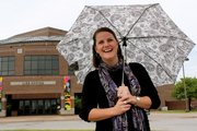 Lied Center Development Director Megan Poindexter takes shelter from the rain outside the Lied Center, 1600 Stewart Dr. Poindexter took the job after working in the adoption field.