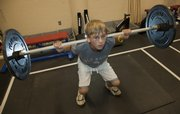 Aaron Foster, 12, demonstrates a back barbell squat at Kansas University's Robinson Gymnasium. Proper technique is a a good starting point for children learning to lift weights.