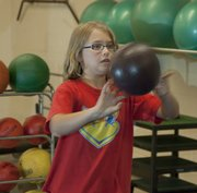 Lindsey Fry, 9, shows how medicine balls are another easy method of early weight training. Proper technique is a a good starting point for children learning to lift weights.