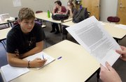 Free State high school senior Sam Walter takes notes as classmate Kelsey Cherland practices a debate scenario at the high school.