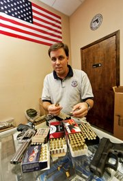 Michael Mayer explains the various types of ammunition for handguns at the Shooters' Club on Aug. 22 in Harahan, La., a suburb of New Orleans.