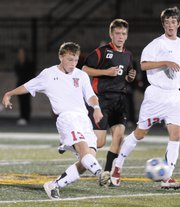 Lawrence High's Cody Campbell, left, moves the ball upfield past Blue Valley West junior Tyler Conway and LHS senior Will Burg. The Lions fell to BV West, 2-0, Monday at LHS.