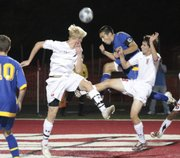 Lawrence High School players Julio Salazar, left and Zach Wustefeld, right, defend against an attempt on goal by a player from Olathe South in a game Tuesday night at LHS.