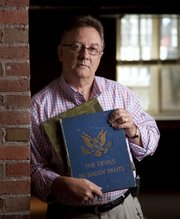 "Kim Mandle displays a book, ""The Devils in Baggy Pants,"" which was written by his father, 1st Lt. William D. Mandle, in 1945 right after World War II. The book chronicles the World War II history of the 504th Parachute Infantry Regiment of the 82nd Airborne Division."