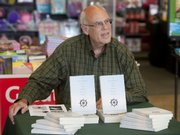"Author Kent Weatherby signs copies his book ""The Frenchman Ate the Fresh Bread First"" recently at Hastings Book Store at 23rd and Iowa streets in Lawrence."