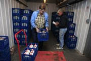 Norm Crawford, left, and Tim Iwig sort and load bottles of milk on a cart Wednesday at Iwig Family Dairy in Tecumseh before delivering the milk to Wichita. Iwig could be faced with closing his business because of record low milk prices, reduced sales because of the recession, and high feed and fuel costs.
