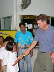 Tom Van Holt, right, hands out supplies to schoolchildren in Khura Buri, Thailand, six months after the Dec. 26, 2004, tsunami. Van Holt is traveling to Manila, Philippines, today to help victims of the recent typhoons.