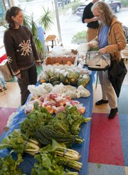 Elizabeth Stevens, right, picks up her allotment of produce Thursday at the Rolling Prairie distribution site at Local Burger. The fresh produce program distributes food to area residents on Mondays at the Community Mercantile Inc. and Thursdays at Local Burger. At left assisting with the distribution is Stephanie Barrows.