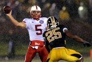 Nebraska quarterback Zac Lee, left, tosses a pass as Missouri's Zaviar Gooden defends. Nebraska won, 27-12, on Thursday night in Columbia, Mo.