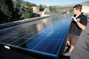 John Shaw, owner of Shaw Solar and Energy Conservation, pauses Aug. 27 next to a portion of a 44-kw grid-tied photovoltaic solar system installed by his company two years prior on the roof of the Smiley Community Building in downtown Durango, Colo.