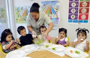 Preschool teacher Jennifer Rosario serves celery to 2-year-olds at the Latin American Community Center in Wilmington, Del. New research from Harvard University shows few states require that child care providers take specific nutrition and physical activity steps to keep the under-5 crowd healthy.