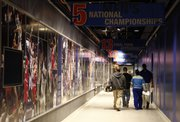 Visitors tour the west hallway of Allen Fieldhouse, which is now decorated with photographs.