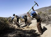 Aaron Wilson, right, of Pasadena, Calif., a recently hired worker with the California Conservation Corps, clears hiking trails with other CCC workers in the San Bernardino National Forest in Hemet, Calif., in this March 16 file photo. Eight of the 18 CCC workers were hired by the U.S. Forest Service as part of the recently approved federal stimulus plan.