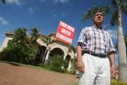 Alfonso Sanchez, pictured outside his Davie, Fla., home Thursday, cannot sell it or rent it — he can only tear the walls down and almost rebuild the house, he said. The $1.7 million home has Chinese drywall throughout the house, and Sanchez says it is now worth nothing.