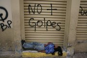 "A woman sleeps under graffiti that reads in Spanish, ""No more coups"" in Tegucigalpa, Honduras, in this Oct. 5 file photo. Hondurans are suffering from a political crisis after the nation's military ousted President Manuel Zelaya. With aid cut off from the U.S. and E.U., an already fragile economy is under even more duress."