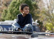 Six-year-old Falcon Heene sits cross-legged Thursday on the roof of his family's van outside his home in Fort Collins, Colo., after the little boy was found hiding in a box in a space above the garage.