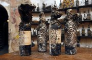 Four bottles of 1875 Armagnac Vieux, covered in a black fungus that looked like matted cat fur and unearthed from a wine cellar this week, are seen Thursday at La Tour d'Argent restaurant in Paris. The restaurant is cleaning out its 450,000-bottle wine cellar — one of the best in the world — and putting 18,000 bottles up for auction in December, an event that has captured the imagination of wine lovers.