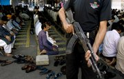 A Pakistani police commando stands guard next to the worshippers offering Friday prayer at a mosque in Lahore, Pakistan. Authorities have beefed up nationwide security after a recent wave of terrorism, which killed many people in different parts of the country. Pakistan is battling a wave of violence by Islamic extremists in its towns and cities and in the lawless border area with Afghanistan in the northwest.