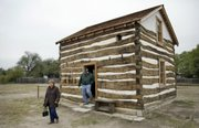 Karan and Steve Snodgrass of Fletcher, Okla., depart the Heller Cabin in Old Cowtown, in Wichita. The cabin dates to 1870 and was recently restored and moved to the entrance of Cowtown.