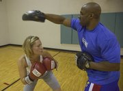 Personal trainer Wayne Jackson and client Kendra Trebilcock work out together at Lawrence Athletic Club, 3201 Mesa Way. Jackson suggests looking for health clubs in areas where you'll travel to for holidays and requesting a one-week pass.