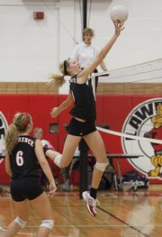 Lawrence High's Lillian Schonewise tips a shot over the net against Emporia. At left is Kendyll Severa. The Lions went 1-1 at their triangular on Tuesday at LHS.