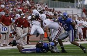 Oklahoma receiver Ryan Broyles spins over Kansas cornerback Ryan Murphy at Kivisto Field, Friday, Oct. 24, 2009. Left are Oklahoma receiver Cameron Kenney and Kansas safety Chris Harris.