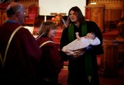 Plymouth Congregational Church associate pastor, the Rev. Josh Longbottom shows off Essie Funk, daughter of Greta and Tyson Funk, during a baptism ceremony on Oct. 18.
