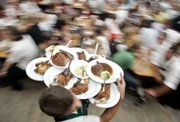 A waiter balances plates with meals at the Munich Octoberfest in Munich, Germany. The annual festival lasts 16 days and is celebrated with German food and beer.