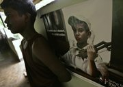 A former Sri Lankan child soldier leans against a wall with a poster showing a child soldier Oct. 1 in a classroom at a government rehabilitation center in the village of Ambepussa, about 40 miles northeast of capital Colombo, Sri Lanka. About 570 children are among an estimated 10,000 former rebels sent to rehabilitation centers after the 25-year war for a separate Tamil state ended in May.
