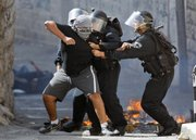 Israeli policemen detain a Palestinian youth during clashes Sunday in the Arab neighborhood of Ras Al Amud  in east Jerusalem. Israeli forces Sunday stormed the Jerusalem's holiest shrine, known to Jews as the Temple Mount and to Muslims as the Noble Sanctuary, firing stun grenades to disperse hundreds of Palestinian protesters who were pelting them with stones.