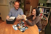Darren and Janet Moore, Lawrence, look over old family photos of times spent with in-laws in western Kansas. The Moores still visit family for the holidays but travel around rather than on Thanksgiving and Christmas to slow down their hectic pace.