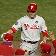 Philadelphia's Chase Utley accepts congratulations after hitting a sixth-inning home run. The Phillies defeated the Yankees, 6-1, on Wednesday night in New York.