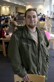 Mike Grace, 24, a student at Wake Technical Community College, visits the campus library Thursday in Raleigh, N.C. A study  by the Pew Research Center shows the share of Americans age 18 to 24 attending college hit a record high in October 2008.