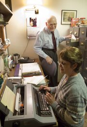 Diane Murry, a medical assistant, uses an electronic typewriter to fill out health insurance forms for Dr. Philip L. Stevens, background, who has used only paper records in his 54 years of practice in Tonganoxie.