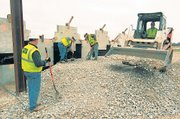 Kenny Mooney, left, watches while Matthew Kuticka and Bob Williams finish shoveling and Justin Hannah, right, moves a load of rock last week at the construction site of an overpass for U.S. Highway 71 south of Lamar, Mo. The employees of JLA Construction, Republic, Mo, said they have been off work for periods of 2009 and don't have prospects for more work after this job is completed in a couple of weeks.