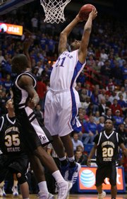 Kansas forward Markieff Morris pulls back for a two-handed dunk over Fort Hays State guard Orrin Greer during the first half of Tuesday&#39;s exhibition at Allen Fieldhouse.
