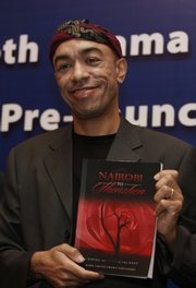 "Mark Ndesandjo, one of President Barack Obama's half siblings, holds his new book ""Nairobi to Shenzhen"" during a news conference today in Guangzhou, a southern city of China. Obama's half brother in China has broken his silence with the media to discuss his new novel: a semi-autobiographical story of self discovery and love that provides a detailed portrait of his abusive father."
