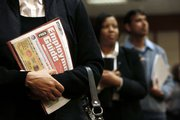 Sonja Jackson, Detroit, holds an Employment Guide while standing in line Wednesday at a job fair in Livonia, Mich. The number of newly laid-off workers filing claims for unemployment benefits last week fell to the lowest level in 10 months, but companies also cited productivity increases that dimmed hopes for more hiring.