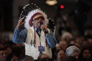Wearing a traditional headdress, Marcus Levings, chairman of the Three Affiliated Tribes, gestures as he asks President Barack Obama a question Thursday during the White House Tribal Nations Conference, which took place at the Interior Department in Washington.