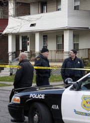 Cleveland police stand watch outside the home of Anthony Sowell on the city's east side Thursday before executing a further search of the house where the remains of 11 people have been discovered.
