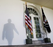 President Barack Obama casts a shadow on the wall as he walks to the podium to speak Friday in the Rose Garden of the White House in Washington.