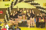 Free State gymnasts, from far left, Camille DuBos, Jackie Soelter, Aly Frydman, Lexi Gonzales, Brooke Leslie, Drue Davis and, holding trophy, Kelcy Bowers, share the state gymnastics podium with Newton High. The teams were named state co-champions after Saturdays meet at Newton.