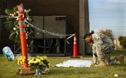 Sgt. 1st Class Noval Alexander pauses to read some of the condolences at a makeshift memorial Saturday at Fort Hood, Texas.